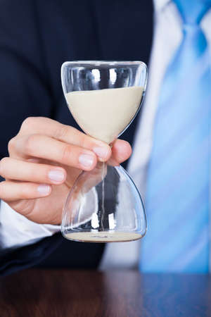 Close-up Of Businessmans Hand Holding A Hourglass photo