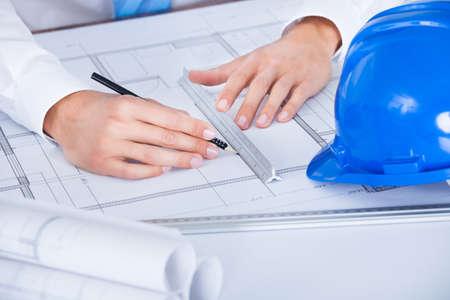 Close-up Van Mannelijke Architect werkzaam op blauwdruk op bureau
