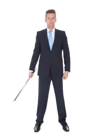 samurai warrior: Young Businessman Standing With Sword Over White Background Stock Photo
