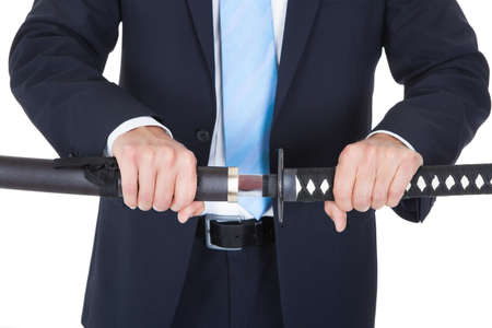 duel: Close-up Of Businessman Removing Sword Over White Background Stock Photo