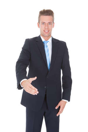 Happy Young Businessman Extending Hand To Shake photo