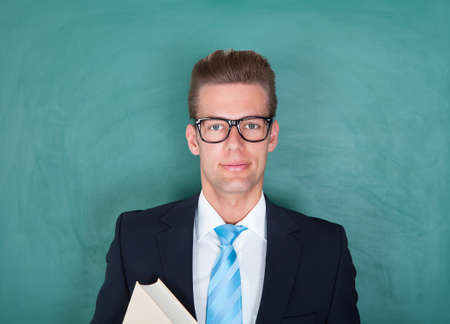 Young Male Lecturer Standing In Front Of Chalkboard photo