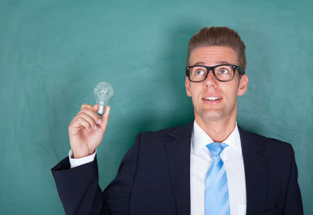 Young Male Professor Holding Light Bulb Against Chalkboard photo