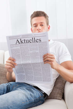 Man Reading Newspaper With The Headline Aktuelles photo