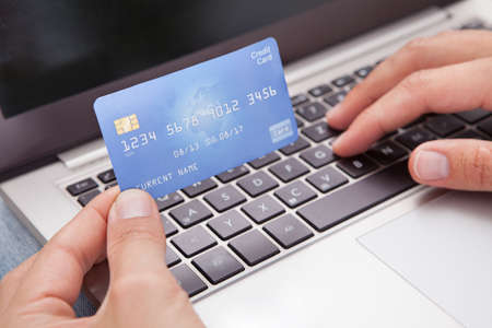 online transaction: Young Man Sitting With Laptop And Credit Card Shopping Online Stock Photo
