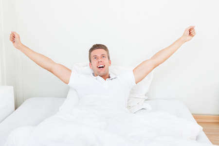 waking up: Young Man Waking Up In Morning And Stretching On Bed