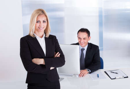 Happy Businesswoman Standing In Front Of Her Colleague Using Computer Stock Photo - 21327787