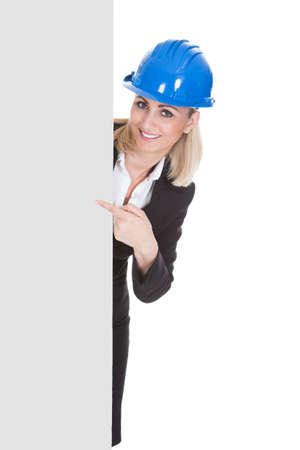 Portrait Of Happy Female Architect Holding Placard Over White Background photo
