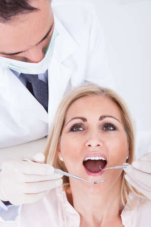 Male Dentist Examining Female Patient In Clinic photo