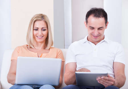 Portrait Of Happy Mid-adult Couple Using Laptop And Digital Tablet photo