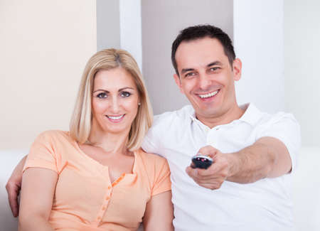 Happy Couple Holding Remote And Watching Television Stock Photo - 21327891