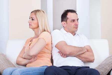 rejection sad: Portrait of mid-adult couple sitting on sofa after quarrel
