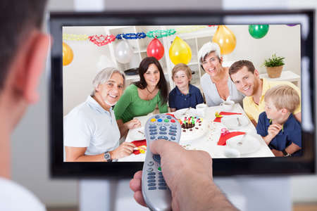 couple watching tv: Close up of hand changing television channel through remote