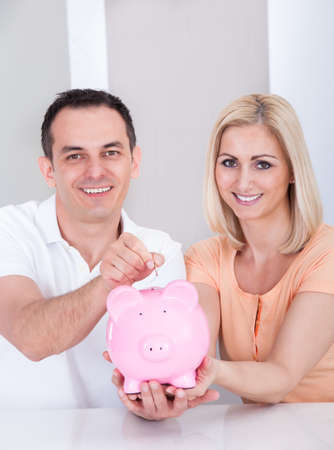 Portrait Of Happy Couple Holding Piggybank Together photo