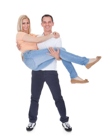 Portrait Of Happy Man Carrying His Girlfriend Over White Background photo