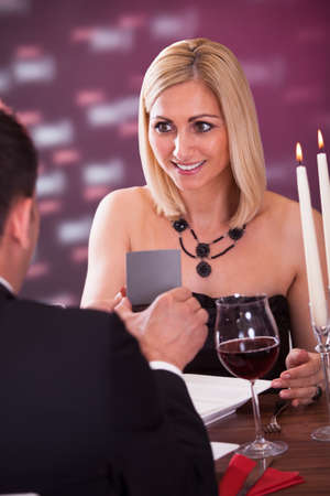 Surprised Woman Looking At Wedding Ring In Restaurant photo