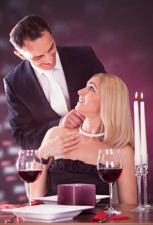 Happy Man Wearing Necklace To Girlfriend In Elegant Restaurant photo