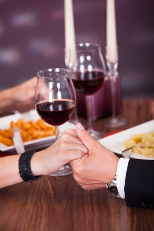 Romantic Couple Holding Each Others Hand At Dinner In An Restaurant photo