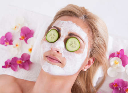 chemical peels: Cosmetician Applying Facial Mask To The Face Of Young Beautiful Woman In Spa Salon