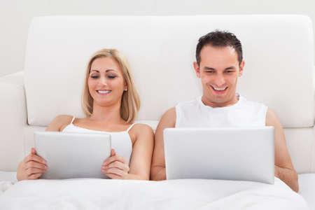 Happy Couple In The Bedroom Using Laptop photo