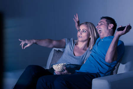 Scared Couple Watching Horror Movie At Home photo