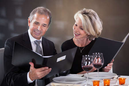 candlelight: Mature Couple Sitting In Restaurant Woman Choosing Menu