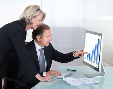 senior business: Happy Mature Businessman And Businesswoman Looking At Graph On Computer Stock Photo