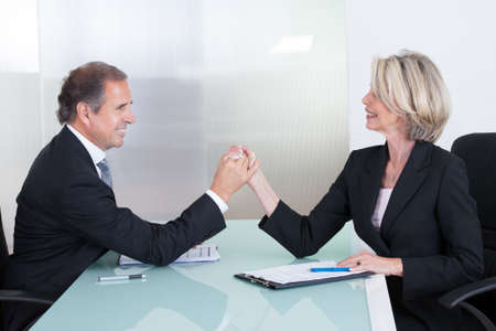 Mature Happy Businessman And Businesswoman Holding Each Others Hand photo