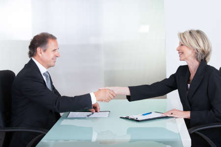 Handshake Of Mature Businesswoman And Businessman In Office photo