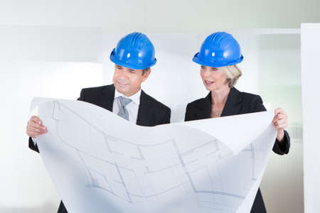 Mature Engineers Looking At Blueprint Wearing Hardhat In Office photo