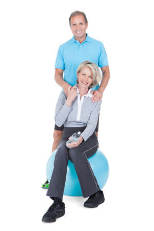 fit ball: Woman Embracing Mature Man From Behind Sitting On Pilates Ball