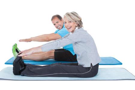 pilates: Happy Mature Couple Exercising Isolated Over White Background