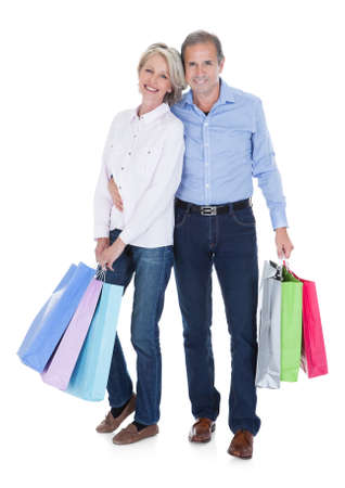 Happy Mature Couple Holding Multi Colored Shopping Bags Over White Background photo