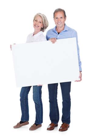 pareja madura feliz: Feliz pareja madura que sostiene el cartel en blanco aislado m�s de fondo blanco Foto de archivo