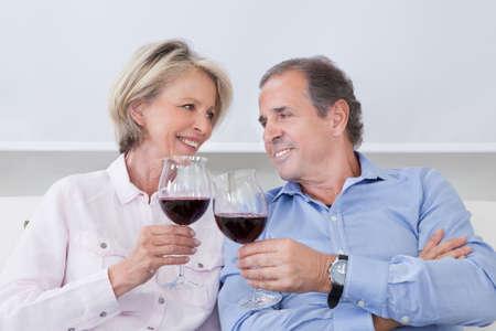 pareja madura feliz: Retrato de la feliz pareja madura sentados lado a lado con Wine Testing