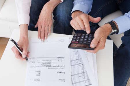 calculadora: Primer plano de una pareja madura haciendo finanzas en el hogar
