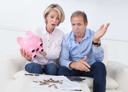 pensioners: Portrait Of Shocked Couple Holding Piggybank At Home Stock Photo