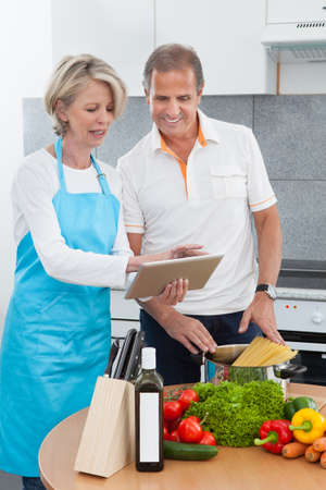 Mature Man And Woman Looking At Recipe Tablet While Cooking In Kitchen Stock Photo - 21328337