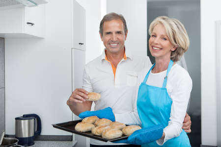 Man Looking At Woman Taking Baking Tray Out From Oven photo