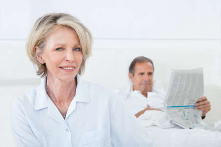 Happy Mature Woman Sitting In Front Of Man Reading Newspaper photo