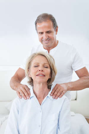 senior man on a neck pain: Mature Man Massaging Womans Shoulder In Bed Stock Photo