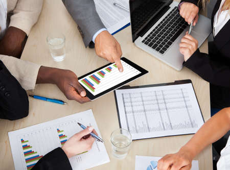 discuss: Multi Ethnic Business Colleagues Discussing Graph On Digital Tablet Stock Photo