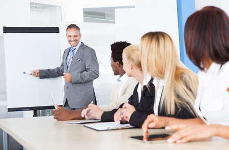 profesor: Empresarios Mirando a negocios que explica en la presentación Foto de archivo