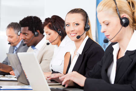 call center: Happy Co-workers Wearing Headsets Working In Call Center