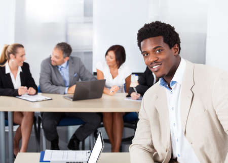 Portrait Of Happy African Businessman Sitting In Front Of Colleagues photo