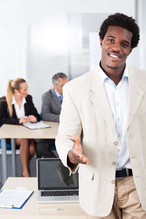 welcome people: Happy African Businessman Offering Handshake In Front Of Colleagues Stock Photo