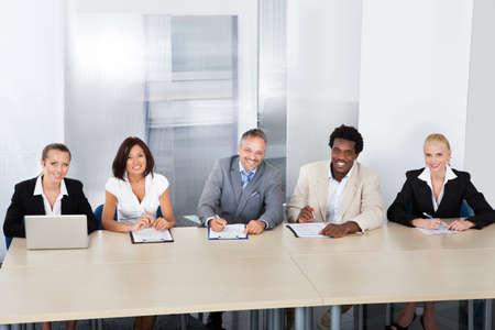 Grupo de Funcionarios de Recursos Humanos Corporativos Sentado en una mesa para tomar Entrevista Foto de archivo - 21328382