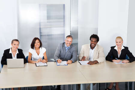 Panel Of Corporate Personnel Officers Sitting At A Table For Taking Interview photo