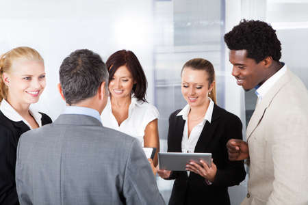 Group Of Happy Multiracial Businesspeople Looking At Digital Tablet photo