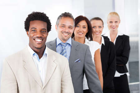 företag: Grupp lyckliga multiracial affärsmän står i en rad